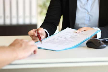 Nahaufnahme eines Executive Hände mit einem Stift und anzeigt, wo ein Vertrag im Büro zu unterzeichnen Standard-Bild