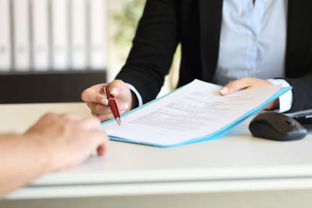 Nahaufnahme eines Executive Hände mit einem Stift und anzeigt, wo ein Vertrag im Büro zu unterzeichnen