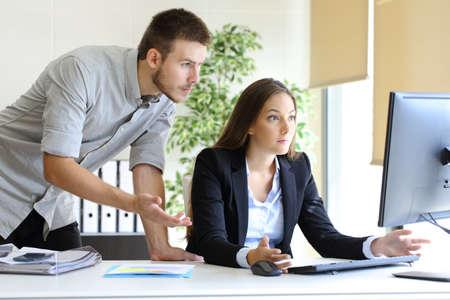 Upset Geschäftsleute versuchen, mit einem Desktop-Computer im Büro Blick auf Monitor auf Linie zu arbeiten