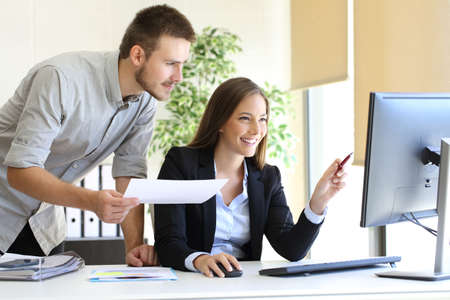 Los empresarios de co-working comparar una información de la computadora de escritorio con el documento de papel en la oficina Foto de archivo