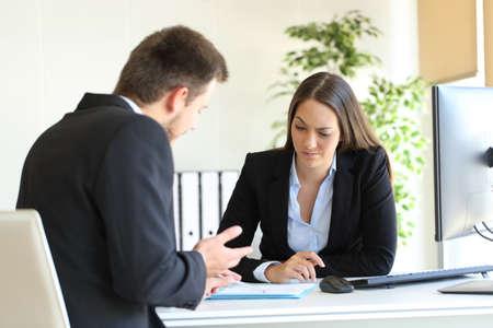 vendedor: Mal hombre de negocios tratando de convencer a un cliente sospechoso durante una negociación difícil en un escritorio en la oficina