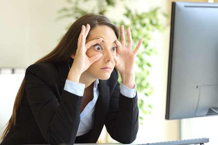 사무실에서 데스크톱 컴퓨터 모니터를 보는 손가락으로 눈을 띄지 않고 깨어있는 졸린 사업가