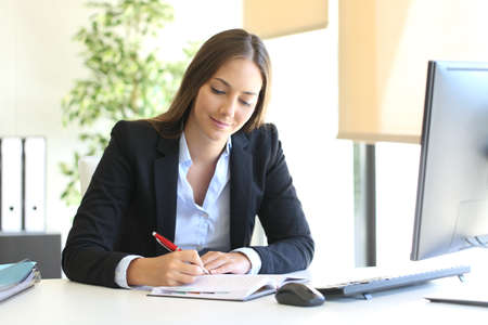 Busy businesswoman writing in an agenda on a desktop at office Imagens
