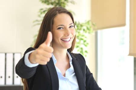 幸せな実業家をジェスチャー親指をポーズと背景のウィンドウにオフィスでカメラ目線