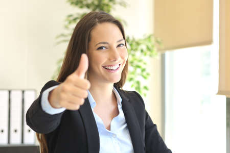 Happy businesswoman posing gesturing thumbs up and looking at camera at office with a window in the background
