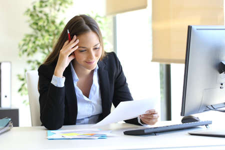 Businesswoman reading a document sitting in a desktop at office