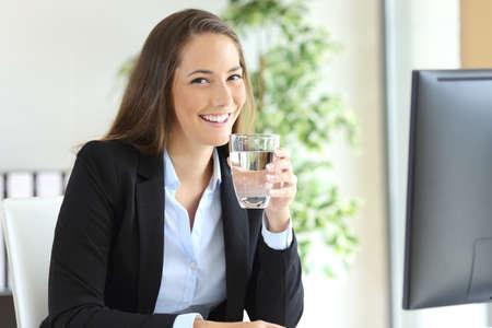 Empresaria lleva el juego que sostiene un vaso de agua en un escritorio y mirando a la cámara en la oficina