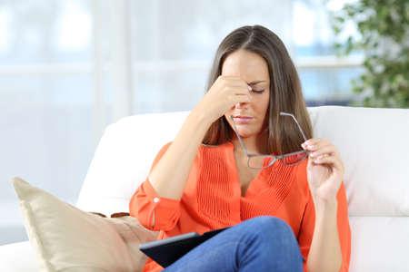Vrouw met een bril lijdt oogstbeest na het lezen van een ebook zit op een bank thuis