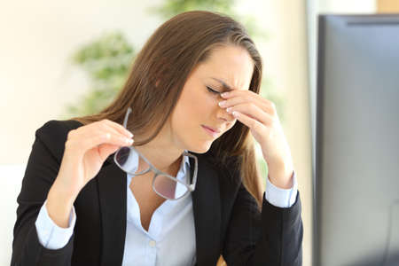 Fatigued businesswoman holding glasses suffering eyestrain in front of a pc screen at office