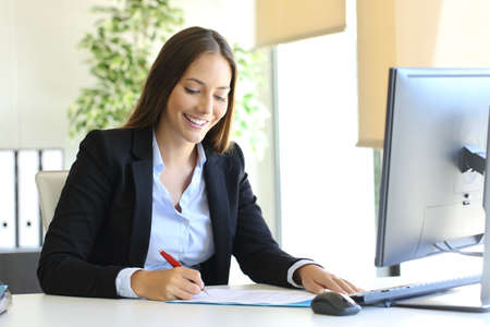 Happy businesswoman signing a contract or document in a desk at office Foto de archivo
