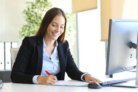 Imprenditrice felice di firmare un contratto o un documento in una scrivania in ufficio
