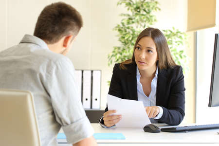 El individuo y la mujer de negocios hablando en una entrevista de trabajo en una oficina Foto de archivo