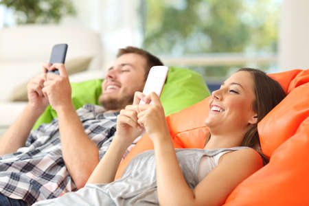 Couple using their smart phones lying on a green and orange poufs in the living room at home