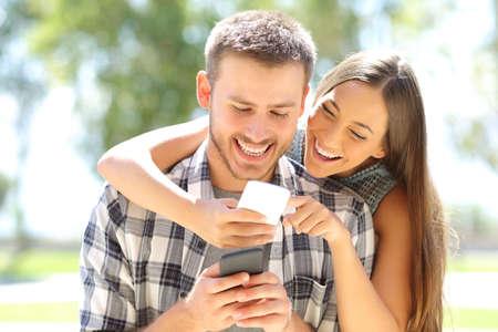Portret van twee vrienden online iedereen met een slimme telefoon in openlucht in een park met een groene achtergrond Stockfoto