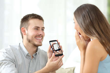 Man asking marriage with the image of the ring in a smart phone Stock Photo