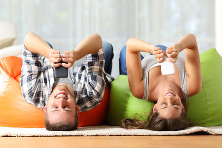 Funny roommates upside down online with their smart phones lying on orange and green poufs in the living room at home Stock Photo
