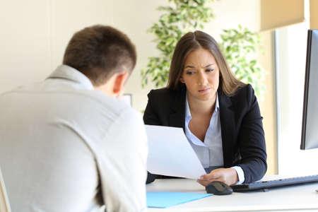 actitud: Empresaria que lee un mal curriculum vitae en una entrevista de trabajo Foto de archivo