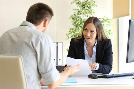 Zakenman die met zijn interviewer spreekt die zijn vaardigheden commentaar geeft tijdens een baangesprek Stockfoto - 69027596
