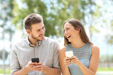 Front view of a couple or friends joking and using smart phones on line outdoors in a park Banco de Imagens