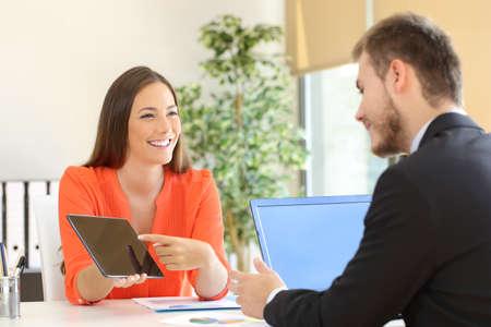 Vendedora tratando de vender productos a un cliente que muestran en una tableta en la oficina