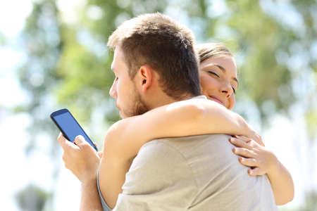 그의 다른 연인과 전화로 문자 메시지를 보내고 그의 무고한 여자 친구를 껴안기. 스톡 콘텐츠