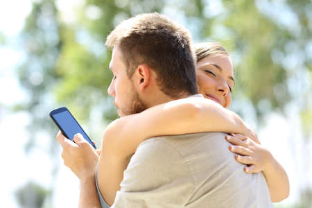 Cheater texting with his other lover on phone and hugging his innocent girlfriend Foto de archivo