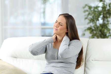 Woman suffering neck ache and complaining sitting on a sofa in the living room at home Stockfoto