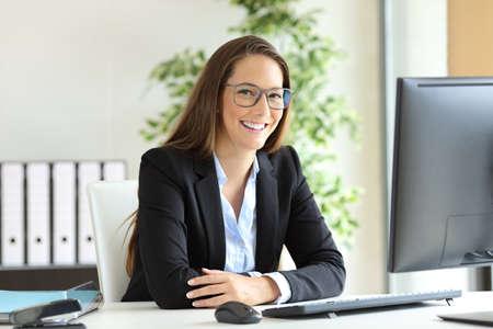 Empresaria feliz vistiendo traje y anteojos que plantea sentarse en un escritorio en la oficina y mirando a ti