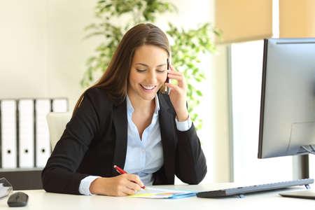 Glückliche Geschäftsfrau, die um Handy ersucht und Kenntnisse auf einem Schreibtisch im Büro nimmt Standard-Bild - 69027606