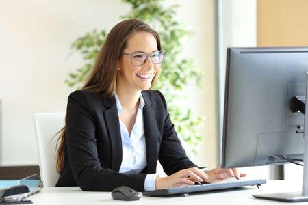 Empresaria llevaba gafas trabajando con una computadora de escritorio en la oficina