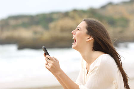 Side view of a exaggerated girl using a smart phone on line and crying desperately with eyes closed on the beach Stock Photo