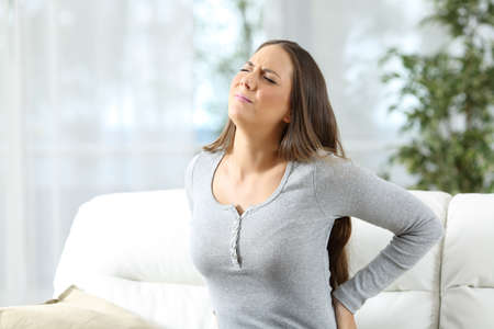 Woman suffering back ache and complaining sitting on a couch in the living room at home