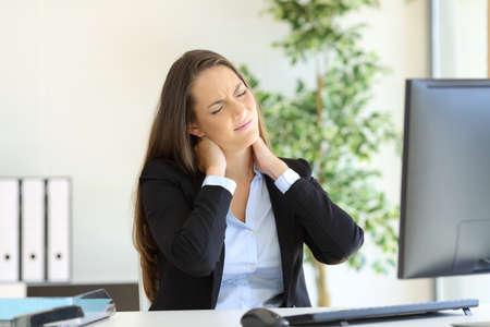 Geschäftsfrau leiden Nackenschmerzen sitzen in einem Stuhl während der Arbeit mit einem Desktop-Computer an ihrem Arbeitsplatz im Büro
