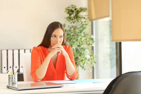 timidity: Thoughtful and nervous woman waiting for the interviewer during a job interview in a desk at office