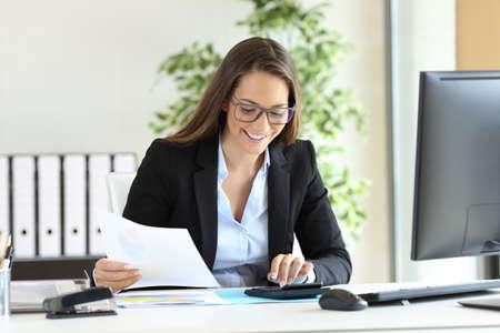 contaduria: Feliz empresaria llevaba traje de trabajo utilizando una calculadora en un escritorio en la oficina