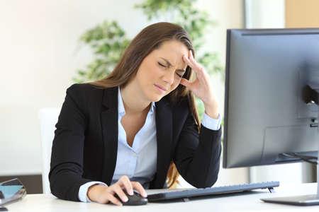 menstruacion: Empresaria sufriendo dolor de cabeza en el trabajo utilizando una computadora de escritorio en la oficina Foto de archivo