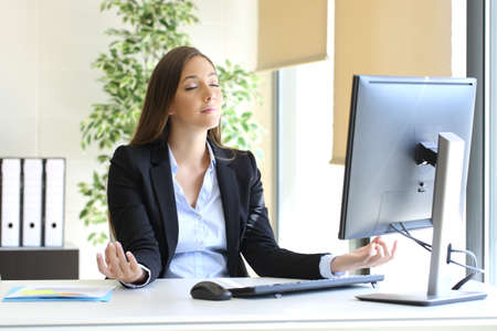 Carefree businesswoman relaxing doing yoga exercises at office Stock Photo