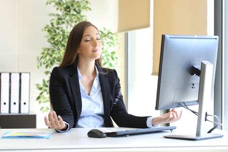 Zorgeloos zakenvrouw ontspannen doet yoga oefeningen op het kantoor