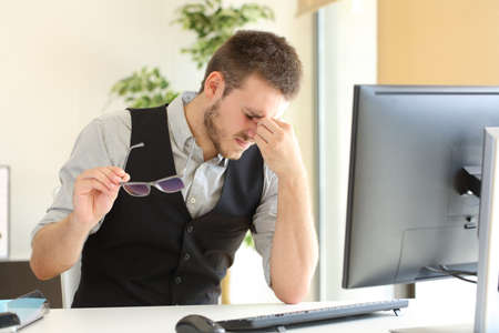 Businessman suffering eyestrain and holding glasses sitting in a desktop at office