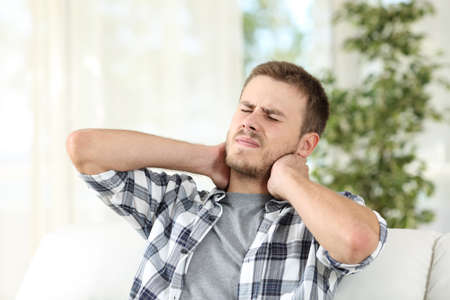 Man suffering neck pain sitting on a sofa in the living room at home Stock Photo
