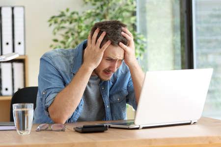 Droevige ondernemer met handen lucht na het lezen van slecht nieuws online met laptop op kantoor