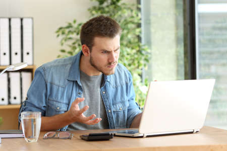 impatience: Angry freelance professional having problems on line with a laptop in a desktop beside a window at office Stock Photo