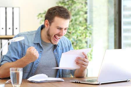 Casual opgewonden ondernemer het lezen van een brief met goed nieuws in een desktop op de werkplek Stockfoto