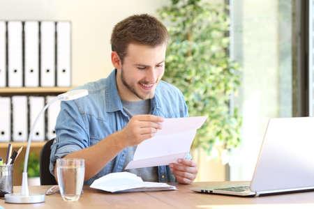Gelukkig ondernemer werken aan het lezen van een brief in een bureau op kantoor