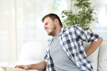 Unhappy man suffering back pain sitting on a sofa in the living room at home