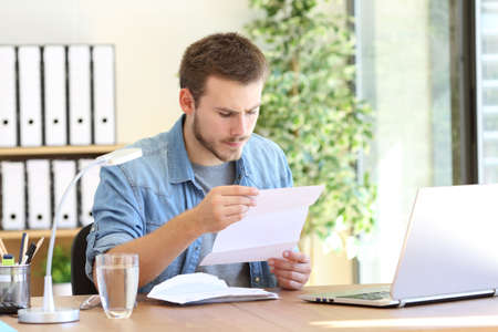 Serious entrepreneur working and reading a letter in a desktop at workplace