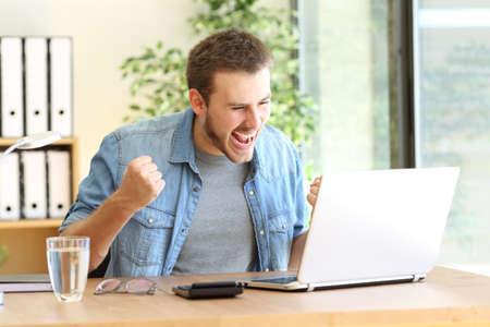ノート パソコンでの作業や職場でラインで良いニュースを読んで興奮している起業家
