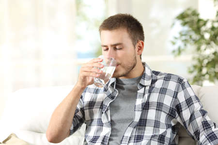 Single man drinking water from a glass sitting on a couch at home Stockfoto