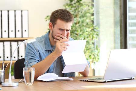 사무실에서 책상에서 나쁜 소식이있는 편지를 읽고 걱정하는 기업가