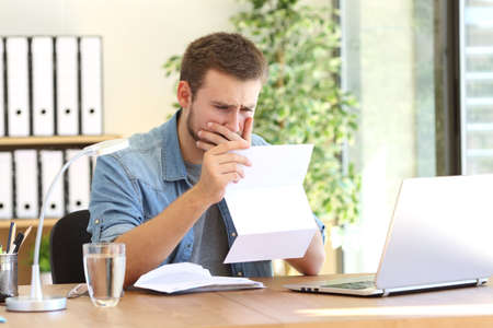 Worried entrepreneur working and reading a letter with bad news in a desk at office